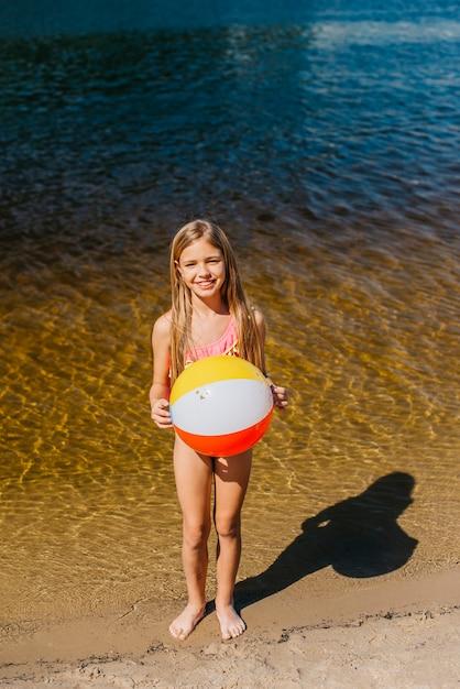Nettes mädchen, welches den wasserball steht gegen meer hält Kostenlose Fotos