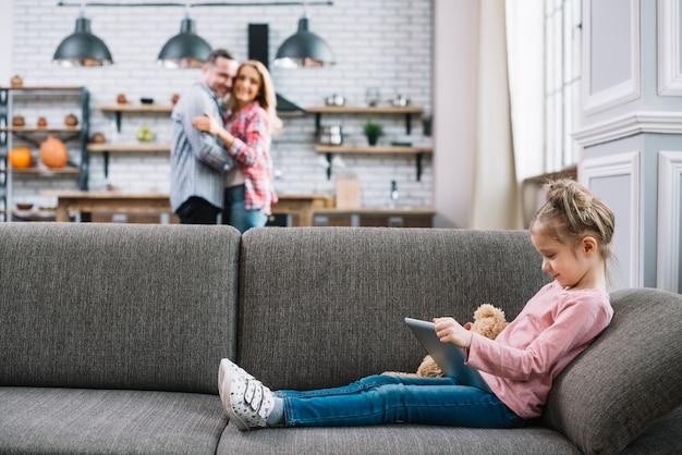 Nettes mädchen, welches die digitale tablette sitzt auf couch verwendet Kostenlose Fotos