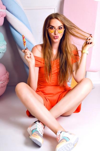 Nettes modeporträt der hübschen blonden frau, süße dekoration, pastellfarben, auf dem boden sitzend und lutscher haltend, tragendes kleid und turnschuhe tragend, lächelnd und spaß. Kostenlose Fotos