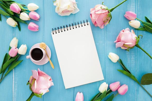 Nettes notizbuch umgeben durch tulpen und rosen auf einem blauen hölzernen Kostenlose Fotos