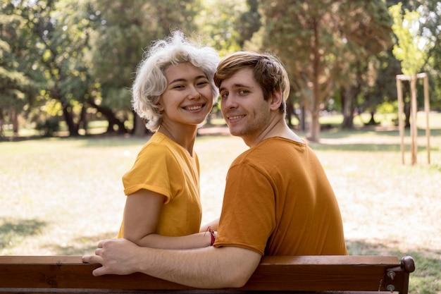 Nettes paar, das auf bank im park aufwirft Kostenlose Fotos