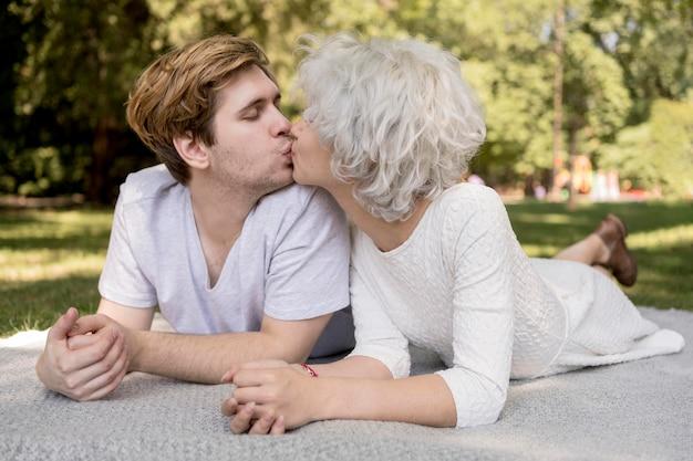 Nettes paar, das draußen auf einer decke küsst Kostenlose Fotos