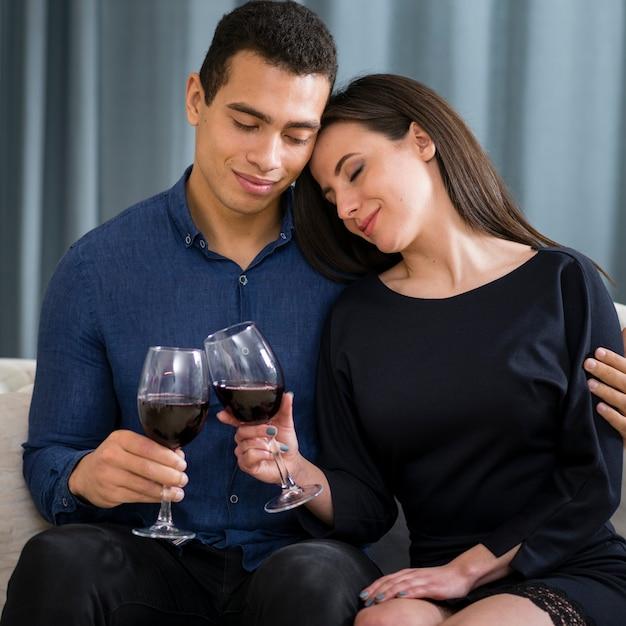 Nettes paar, das ein glas wein beim sitzen auf der couch hat Kostenlose Fotos