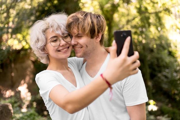 Nettes paar, das selfie zusammen im park nimmt Kostenlose Fotos