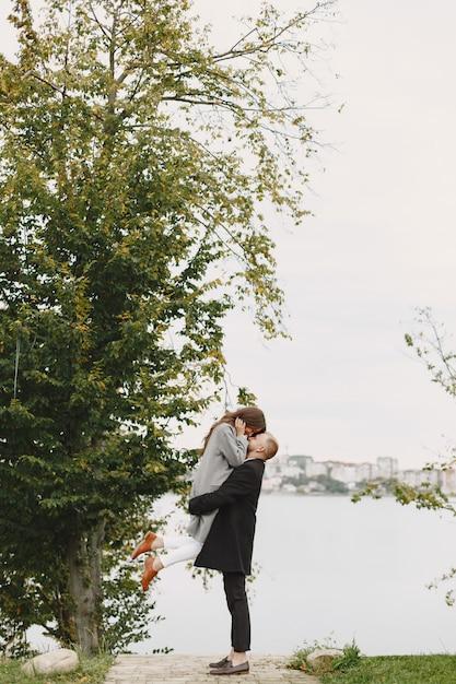 Nettes paar in einem park. dame in einem grauen mantel. leute am pier. Kostenlose Fotos