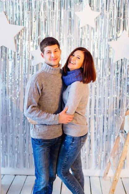 Nettes paar in grauen identischen pullovern umarmt und lächelt für eine kamera Premium Fotos