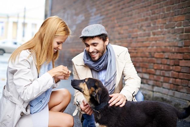 Nettes paar mit ihrem hund auf der straße Kostenlose Fotos