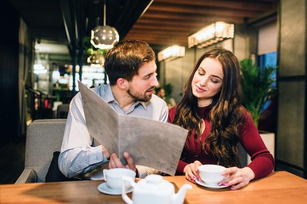 Nettes paar sitzt zusammen in einem restaurant. sie trinkt tee und schaut auf ein menü, während ihr freund versucht, essen für sie zu pflücken. außerdem gibt er ihr ratschläge zum essen. Premium Fotos
