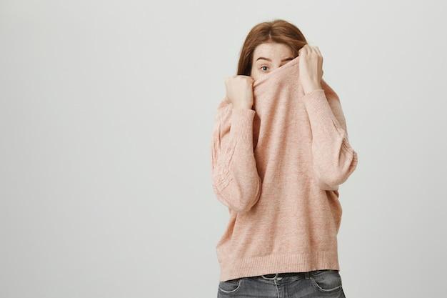 Nettes rothaariges junges mädchen verstecken gesicht über pullover, spähend Kostenlose Fotos