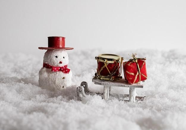 Nettes schneemannspielzeug, schlitten und bunte geschenkboxen im schnee Kostenlose Fotos