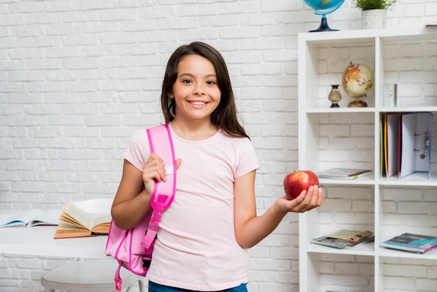 Nettes schulmädchen, das mit rucksack und apfel im klassenzimmer steht Kostenlose Fotos