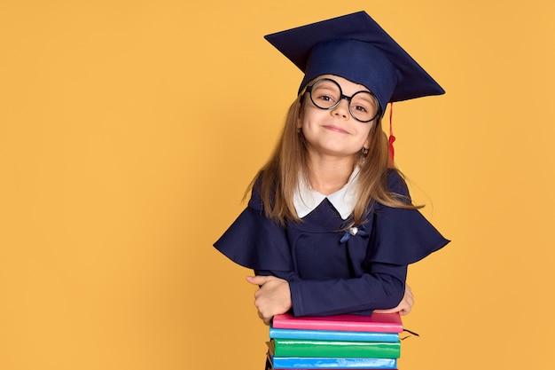 Nettes schulmädchen in der staffelungsausstattung lächelnd beim lehnen auf stapel von lehrbüchern Premium Fotos