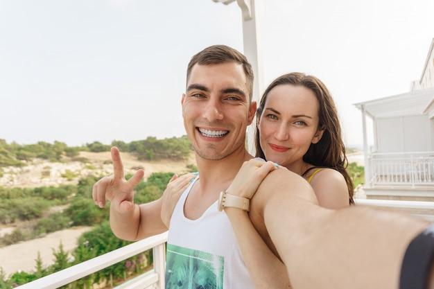 Nettes selfie eines jungen paares, das an der kamera, ein symbol des friedens umarmt und lächelt Premium Fotos