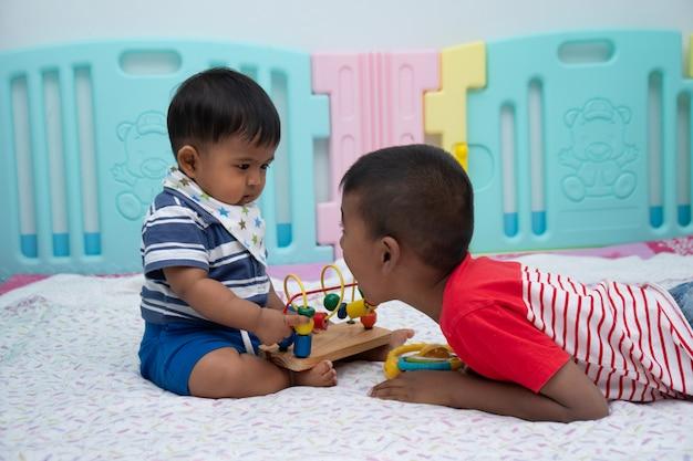 Nettes spiel mit zwei kleinen jungen im raum Premium Fotos