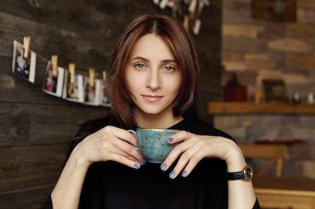Nettes studentenmädchen mit blauen nägeln, die becher halten und frischen cappuccino am kaffeehaus genießen Kostenlose Fotos