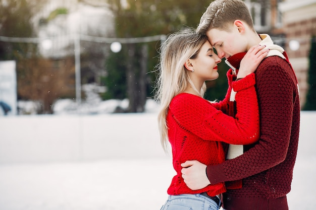 Nettes und liebevolles couplein rote strickjacken in einer winterstadt Kostenlose Fotos