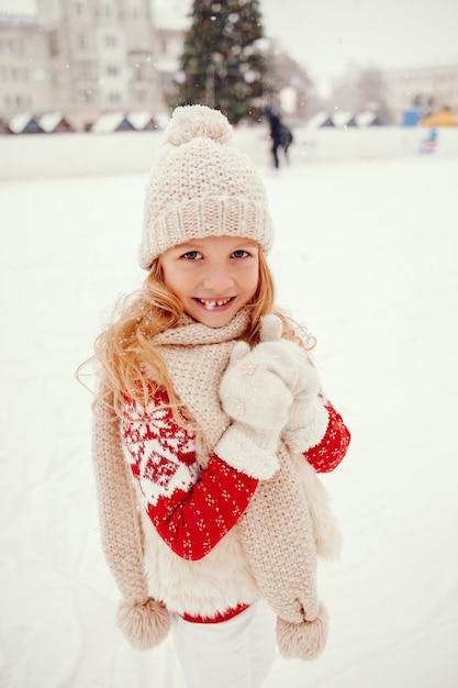 Nettes und schönes kleines mädchen in einer winterstadt Kostenlose Fotos