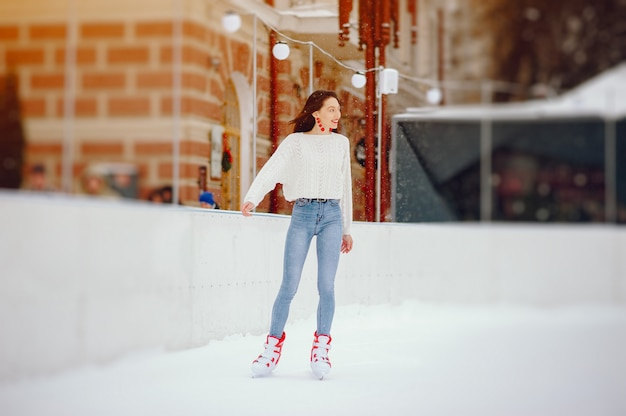 Nettes und schönes mädchen in einer weißen strickjacke in einer winterstadt Kostenlose Fotos