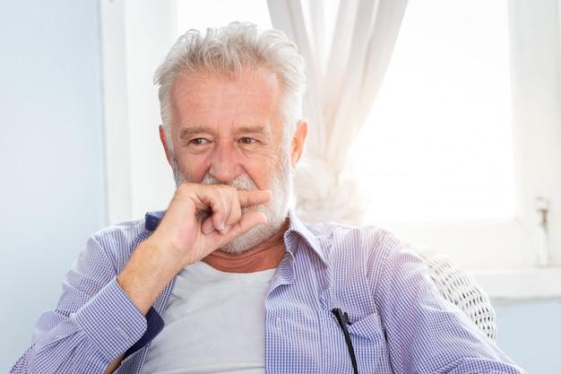 Nettes versteckendes lächeln des älteren alten mannes schauen schüchternes sitzen im raum mit fenster. Premium Fotos