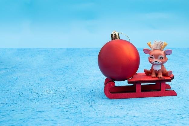 Nettes weihnachten mit rotem weihnachtsball-rentier, das auf einem schlitten sitzt. Premium Fotos
