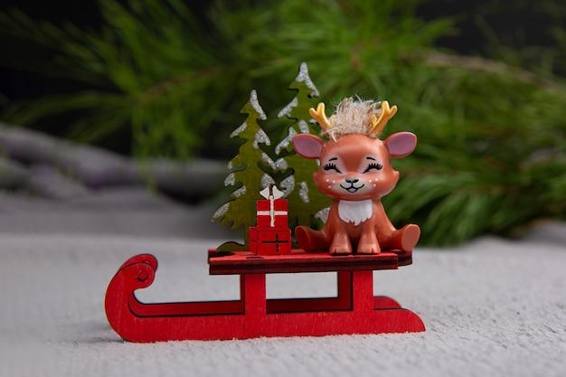 Nettes weihnachtsrentier, das auf einem schlitten-konzept der weihnachtsglücklichen neujahrspostkarte sitzt Premium Fotos