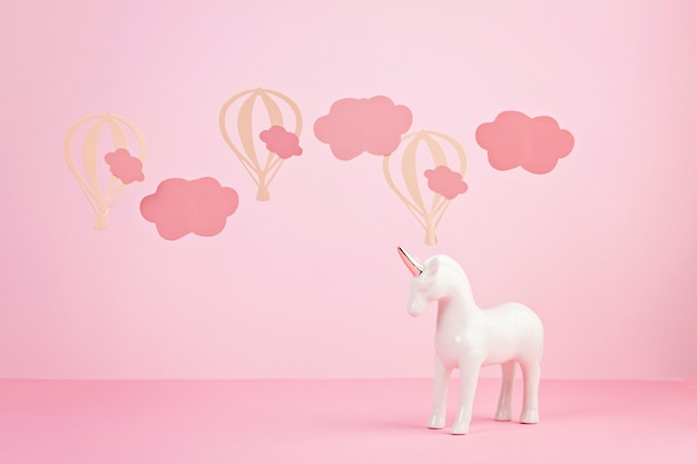 Nettes weißes einhorn über dem rosa pastellhintergrund mit wolken und baloons Premium Fotos