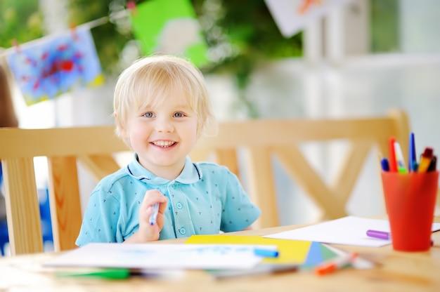 Nettes zeichnen und malen des kleinen jungen mit bunten markierungen am kindergarten Premium Fotos