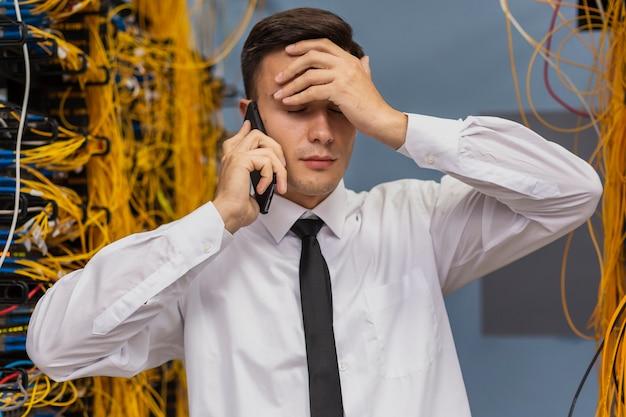 Netzwerktechniker, der am telefonmediumschuß spricht Kostenlose Fotos