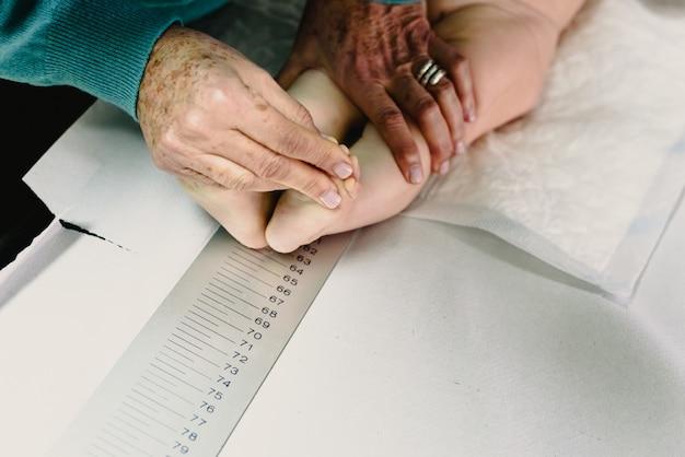 Neu geboren in der klinik des kinderarztes, die mithilfe eines lineals die höhe und höhe des babys misst. Premium Fotos