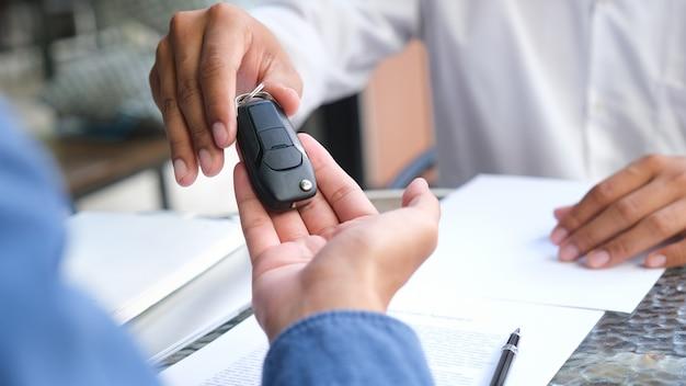Neue autobesitzer nehmen schlüssel von männlichen verkäufern entgegen. Premium Fotos