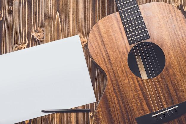 Neue braune gitarre auf holzbrett Premium Fotos