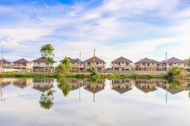 Neue hausbaureflexion mit wasser im see auf wohnbaustelle mit wolken und blauem himmel Premium Fotos