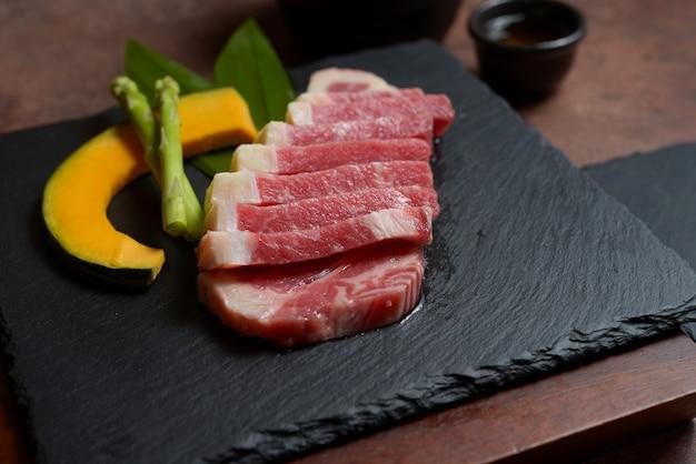 Neue rohe rindfleischbrustscheibe mit kürbisstücken und spargel auf dem schwarzen tellerfelsen, menüsatz. Premium Fotos