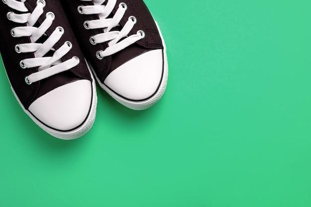 Neue saubere blaue athletische turnschuhe mit weißen spitzeen, auf einem grünen pastellhintergrund. Premium Fotos