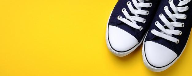 Neue saubere blaue sport-turnschuhe mit weißen spitzeen, auf einem hellen gelben hintergrund. banner. Premium Fotos