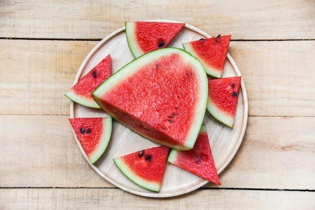 Neue wassermelonenscheibe auf hölzernem behälter Premium Fotos