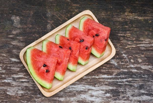 Neue wassermelonenscheibe - tropische frucht der wassermelone auf hölzernem behälter, draufsicht Premium Fotos