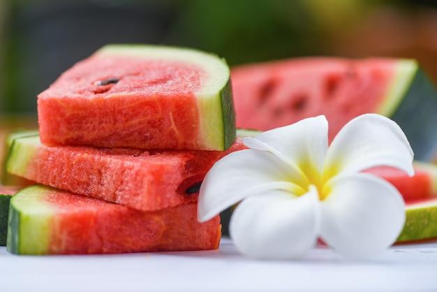 Neue wassermelonenscheibe und weißes flowe Premium Fotos