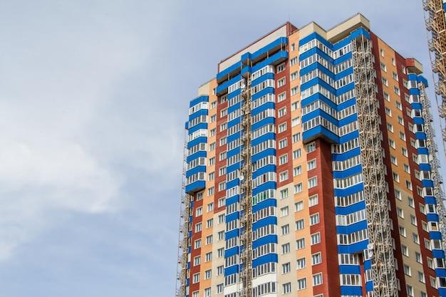 Neuer block der modernen wohnungen mit balkonen und blauem himmel Premium Fotos