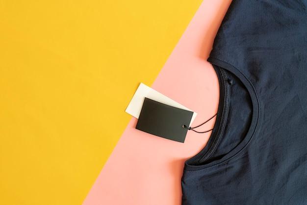 Neues beiläufiges t-shirt mit verkaufspreisschild mit dem exemplarplatz getrennt auf rosafarbenem und gelbem hintergrund. Premium Fotos