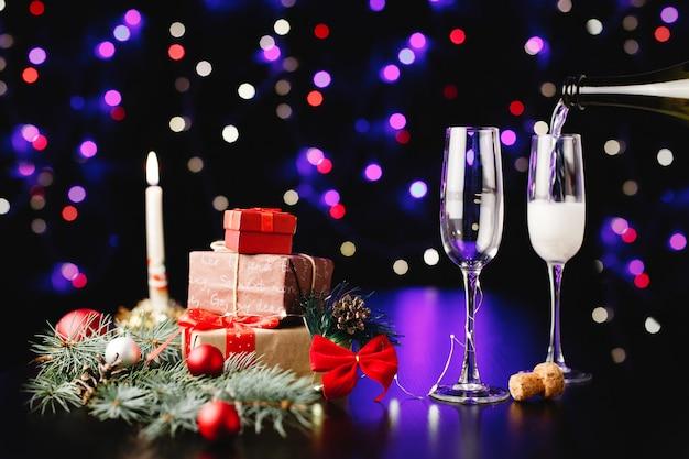 Neues jahr und weihnachtsdekor. jemand gießt champagner in die gläser Kostenlose Fotos