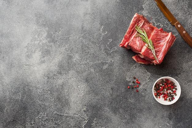 Neues rohes stück rindfleischrippe mit fleisch auf einer dunklen betondecke Premium Fotos