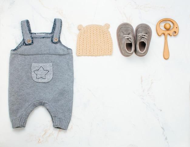 Neugeborene babykleidung und sitzsack auf hellem marmor Premium Fotos