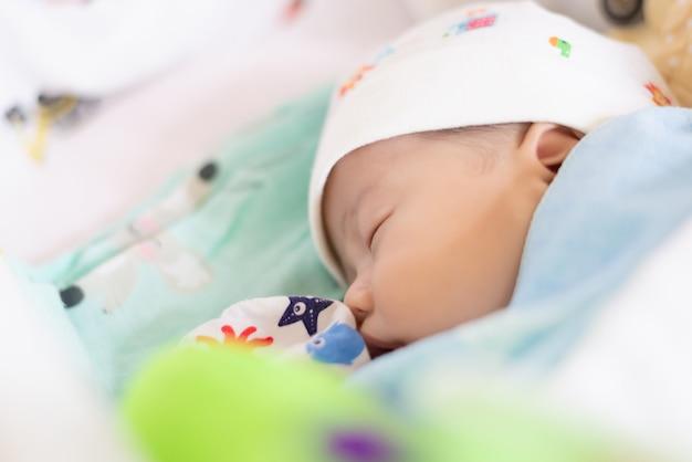 Neugeborene und mothercare-konzept. säuglingsbaby-asiatisches jungenschlafen Premium Fotos