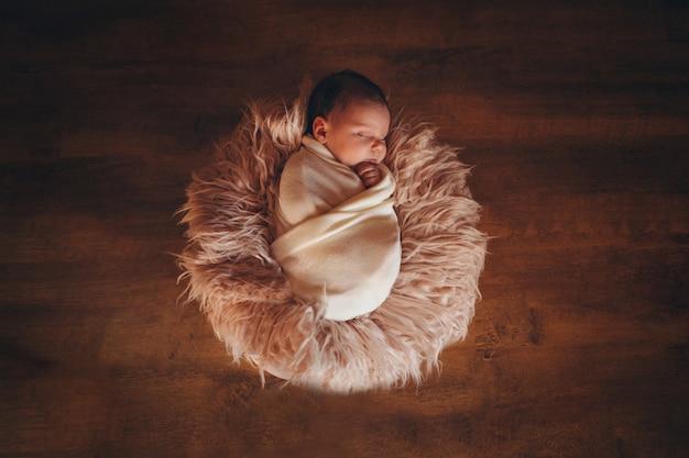 Neugeborenes baby eingewickelt in einer decke, die in einem korb schläft. konzept der kindheit, gesundheitswesen, ivf Premium Fotos