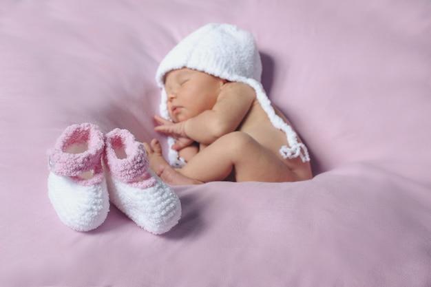 Neugeborenes baby in der weißen strickmütze und in einem paar weißen und rosa schuhen des babys Premium Fotos