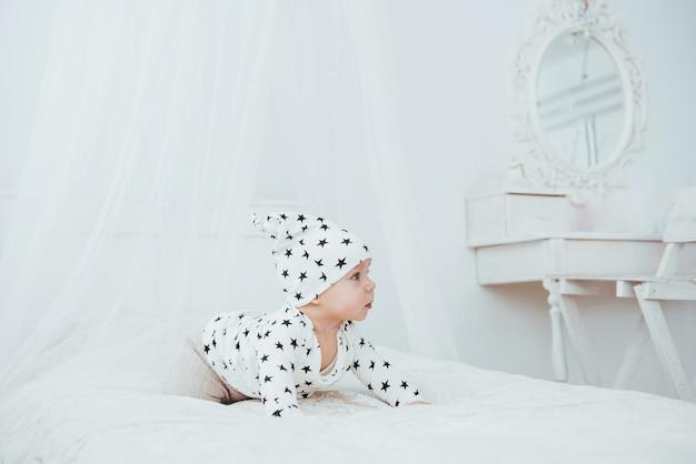 Neugeborenes baby in einem weißen anzug und schwarzen sternen ist ein weißes weiches bett im studio Premium Fotos