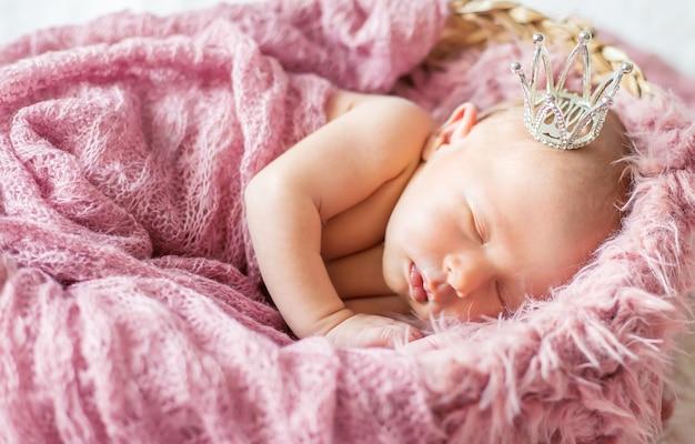 Neugeborenes baby in einer mädchenkrone. selektiver fokus. menschen. Premium Fotos