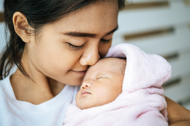 Neugeborenes baby schläft in den armen der mutter und duftet auf der stirn des babys Kostenlose Fotos