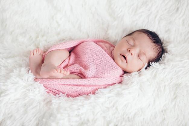 Neugeborenes baby schläft in einer decke eingewickelt. Premium Fotos